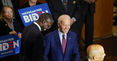 Michigan Lt. Governor Garlin Gilchrist shake the hand of former Vice President Joe Biden after introducing U.S. Sen. Cory Booker to speak while making a campaign stop at Berston Field House in Flint on Monday, March 9, 2020.