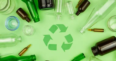 Green recycle sign symbol with glass trash garbage bottle, pills and tubes on green isolated background. Ecology recycle, environment issue, safe planet, refuse reuse recycle concept
