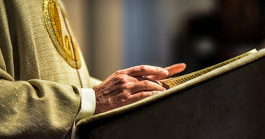 Hands of catholic priest reading a bible