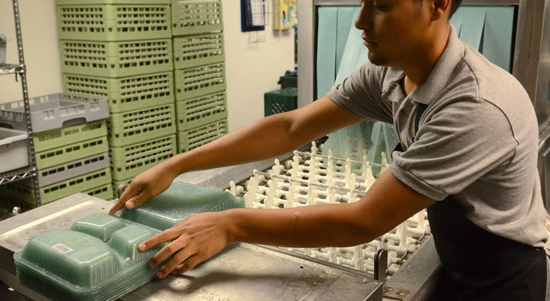 Antoni Fajaro, student from Los Angeles, washes re-usable go containers that students used to fill with food, then they are inserted into the OZZI machine which refunds the $5 deposit on the tray.