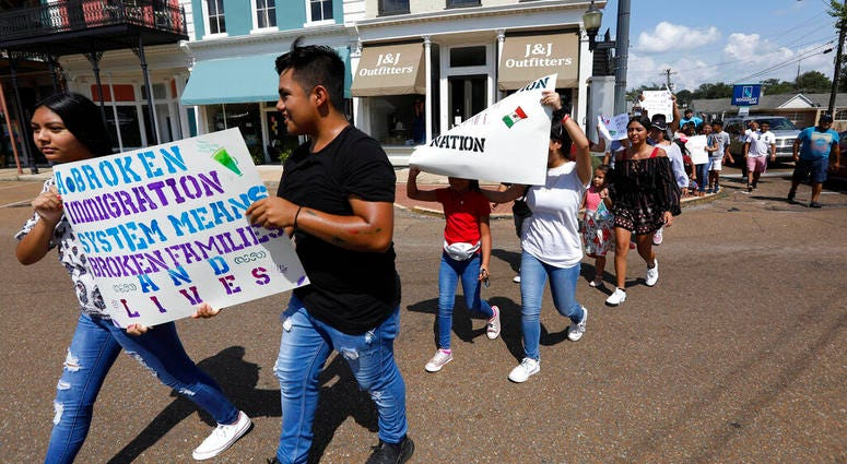 children of mainly Latino immigrant parents hold signs in support of them