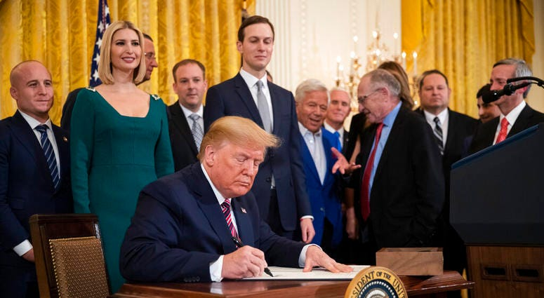 President Donald Trump signs an executive order combatting anti-Semitism in the U. S. during a Hanukkah reception in the East Room of the White House Wednesday, Dec. 11, 2019, in Washington.