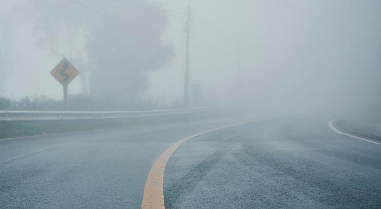 foggy rural asphalt highway perspective with white line, misty road, Road with traffic and heavy fog, bad weather driving - stock photo