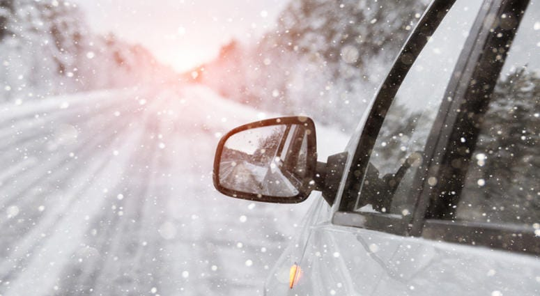 The winter road is reflected in the car's rear-view mirror