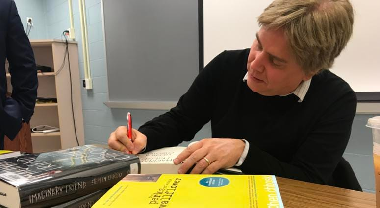 Author Stephen Chbosky signs a book while sitting at a desk
