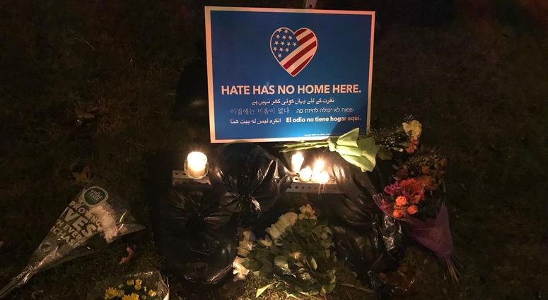 "flowers and candles beneath a sign that reads ""Hate has no home here."""