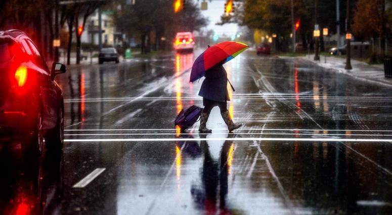 A pedestrian carries a colorful umbrella