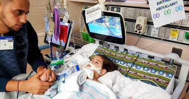 Ali Hassan with his dying 2-year-old son Abdullah in a Sacramento hospital