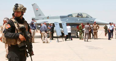 a member of the Iraqi SWAT team stands guard as security forces and others gather next to a U.S.- made F-16 fighter jet during the delivery ceremony at Balad air base, Iraq.