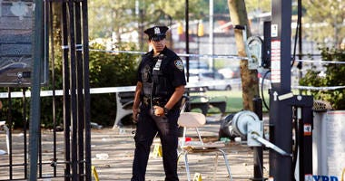A police officer walks by yellow evidence markers at a playground in the Brownsville neighborhood in the Brooklyn borough of New York, Sunday, July 28, 2019. Police said, one man was killed and at least 11 others were injured in a shooting late Saturday n