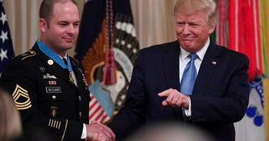 President Donald Trump, right, shakes hands with U.S. Army Master Sgt. Matthew Williams, left, currently assigned to the 3rd Special Forces Group
