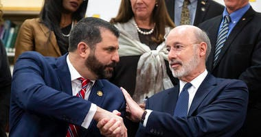 Pennsylvania Gov. Tom Wolf, right, shakes hands with Rep. Mark Rozzi, D-Berks, after signing legislation into law at Muhlenberg High School in Reading, Pa., Tuesday, Nov. 26, 2019. Wolf approved legislation Tuesday to give future victims of child sexual a