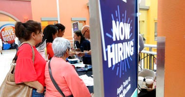 people wait in line to inquire about job openings with Marshalls during a job fair at Dolphin Mall in Miami. On Friday, Dec. 6, the U.S. government issues the November jobs report.