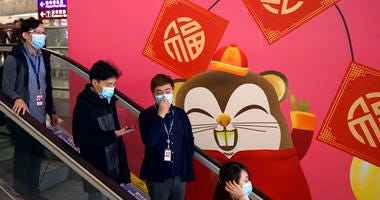 People wear face masks as they ride an escalator at the Hong Kong International Airport