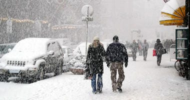 People walking down sidewalks in a snow storm in a city
