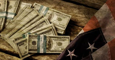 Old USA flag and dollars. Cash laying beside aged flag