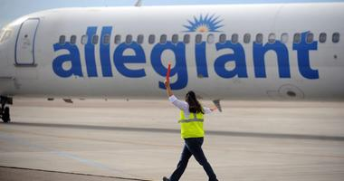 An Allegiant Airlines worker helps taxi a plane for takeoff during the last day of business for Allegiant Airlines