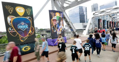 People walk on a bridge lined with video boards providing news on draft picks on the final day of the NFL football draft Saturday, April 27, 2019, in Nashville, Tenn. (