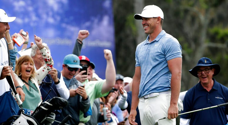 Brooks Koepka shares a laugh with the gallery after chipping onto the 18th green during the third round of The Players Championship golf tournament Saturday, March 16, 2019, in Ponte Vedra Beach, Fla