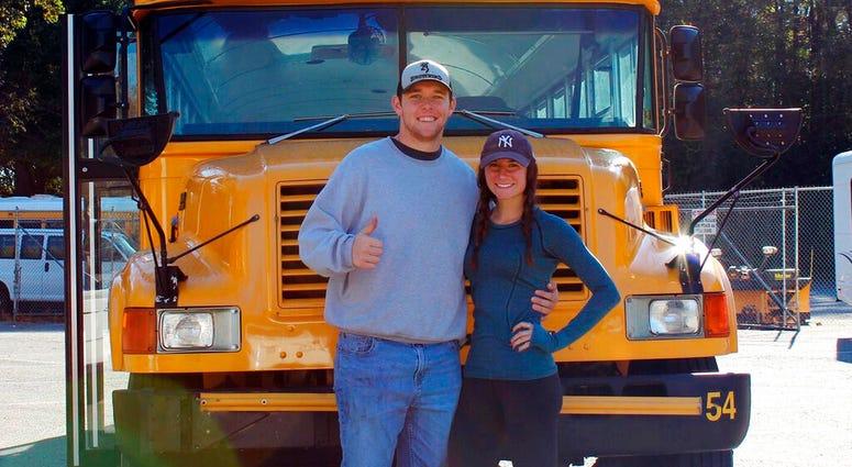 Jack Labosky, left, and Madi Hiatt pose after purchasing a school bus in Lynchburg, Va.
