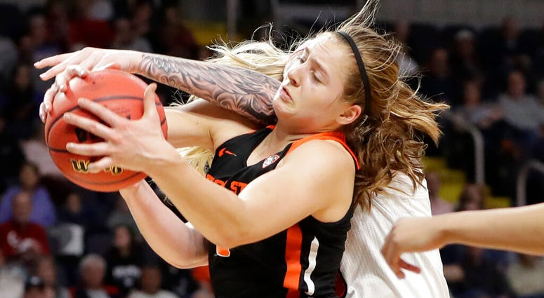 Oregon State guard Mikayla Pivec (0) battles for the ball with Louisville forward Sam Fuehring during the first half of a regional semifinal game in the NCAA women's college basketball tournament, Friday, March 29, 2019, in Albany, N.Y.