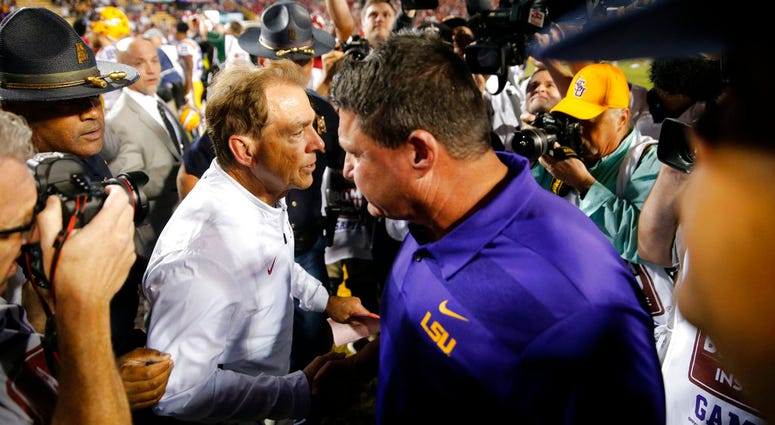 Alabama head coach Nick Saban, left, shakes hands with LSU head coach Ed Orgeron