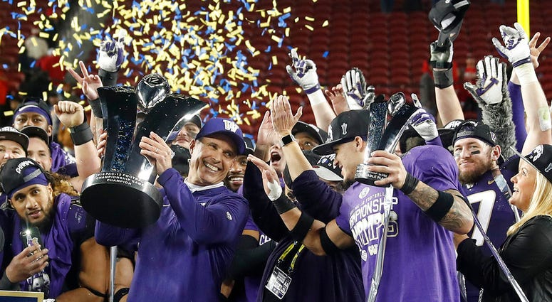 Washington coach Chris Petersen, center left, and defensive back Byron Murphy, center right, celebrate after Washington defeated Utah 10-3 in the Pac-12 Conference championship