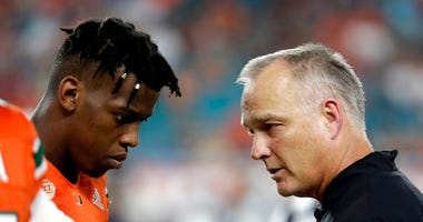 Miami quarterback N'Kosi Perry, left, talking with Miami head coach Mark Richt