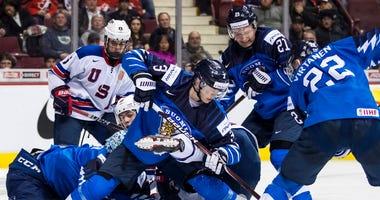 Finland goalie Ukko-Pekka Luukkonen, left, stops United States' Noah Cates