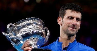 Serbia's Novak Djokovic holds his trophy after defeating Spain's Rafael Nadal in the men's singles final at the Australian Open tennis championships