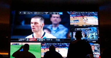 customers watch a game during the NCAA March Madness college basketball tournament at the Hard Rock casino in Atlantic City N.J. Casinos in eight states are opening or expanding retail sportsbooks to capture in-person sports betting business, even while m