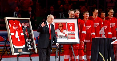 former Detroit Red Wings player Red Kelly waves during his jersey retirement ceremony before an NHL hockey game against the Toronto Maple Leafs in Detroit. Kelly, a defenseman-turned-center whose Hall of Fame career included eight Stanley Cups while playi