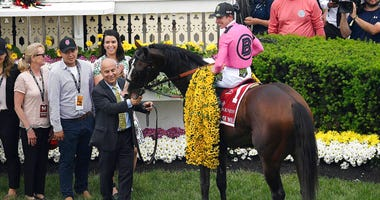 Jockey Tyler Gaffalione sits aboard War of Will as trainer Mark Casse holds the reins after winning the Preakness Stakes horse race at Pimlico Race Course, Saturday, May 18, 2019, in Baltimore.