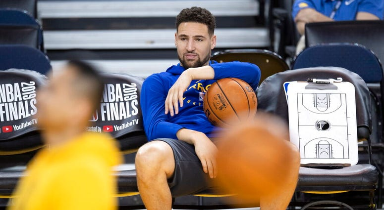 Golden State Warriors' Klay Thompson sits on the bench watching teammates during practice for the NBA Finals against the Toronto Raptors Tuesday, June 4, 2019, in Oakland, Calif. Game 3 of the NBA Finals is Wednesday, June 5, 2019, in Oakland, Calif.
