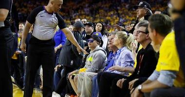 referee Marc Davis, left, gestures toward Golden State Warriors investor Mark Stevens