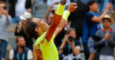 Spain's Rafael Nadal celebrates his record 12th French Open tennis tournament title after winning his men's final match against Austria's Dominic Thiem in four sets, 6-3, 5-7, 6-1, 6-1, at the Roland Garros stadium in Paris, Sunday, June 9, 2019.