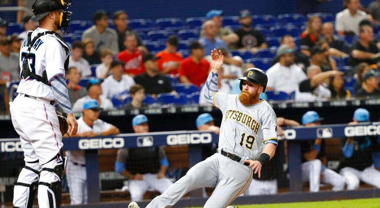 Pittsburgh Pirates' Colin Moran (19) slides into home as Miami Marlins catcher Bryan Holaday looks on during the fourth inning of a baseball game, Sunday, June 16, 2019, in Miami. Moran scored on a double by Jung Ho Kang.