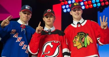 New York Rangers draft pick Kaapo Kakko, left; New Jersey Devils pick Jack Hughes, center; and Chicago Blackhawks pick Kirby Dach pose for photos during the first round of the NHL hockey draft