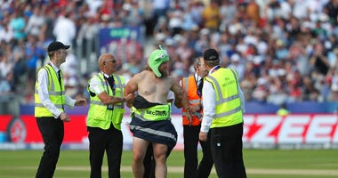 A streaker runs into the field during the Cricket World Cup match between New Zealand and England in Chester-le-Street, England, Wednesday, July 3, 2019.