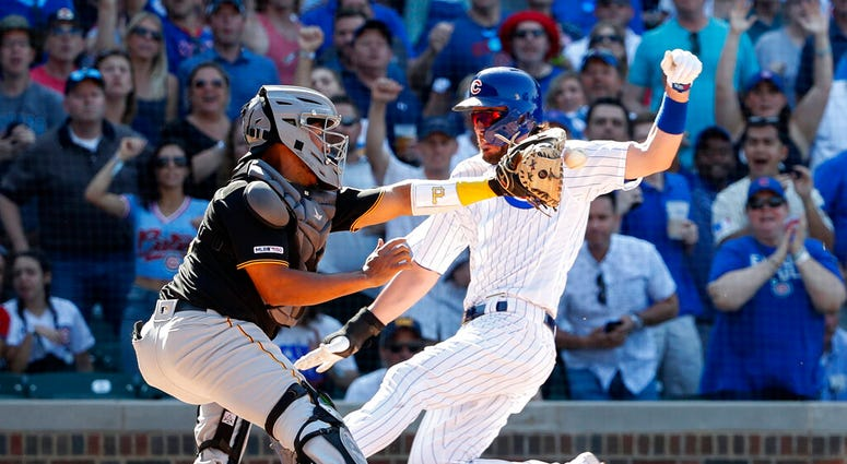 Chicago Cubs' Kris Bryant, right, scores against Pittsburgh Pirates' Jacob Stallings, left, during the eighth inning of a baseball game, Friday, July 12, 2019, in Chicago.