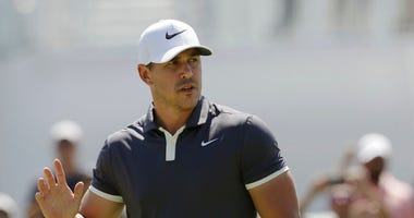 Brooks Koepka acknowledges applause after putting on the first hole of the final round in the Northern Trust golf tournament at Liberty National Golf Course, Sunday, Aug. 11, 2019 in Jersey City, N.J.