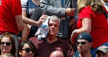 Fenway Park personnel attend to a fan who was hit by a broken bat