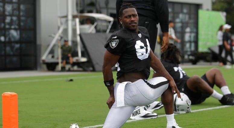 Oakland Raiders' Antonio Brown stretches during NFL football practice in Alameda, Calif., Tuesday, Aug. 20, 2019.