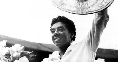 Althea Gibson smiles as she holds her trophies she won by capturing the National women's singles tennis championship at the West Side Tennis Club in Forest Hills, N.Y.