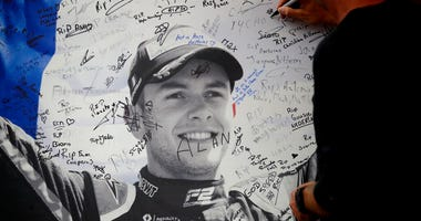 A man signs a remembrance board for Formula 2 driver Anthoine Hubert