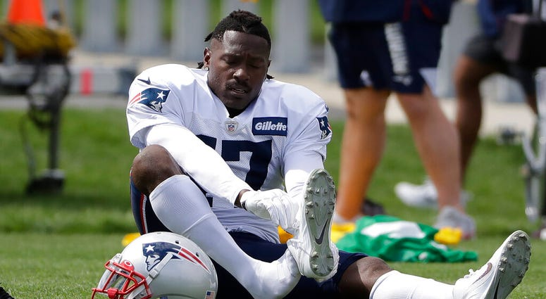 New England Patriots wide receiver Antonio Brown puts on his shoe during an NFL football practice, Wednesday, Sept. 18, 2019, in Foxborough, Mass.
