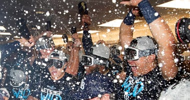 Tampa Bay Rays players celebrate in the clubhouse after they defeated the Toronto Blue Jays and clinched an MLB American League wild-card berth in Toronto, Friday, Sept. 27, 2019.