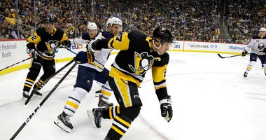 Pittsburgh Penguins' Sidney Crosby (87) can't get his stick untangled from Buffalo Sabres' Vladimir Sobotka during the period of an NHL hockey game in Pittsburgh, Thursday, Oct. 3, 2019.