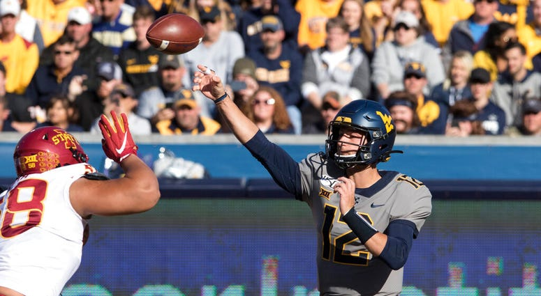 West Virginia quarterback Austin Kendall (12) attempts a pass during the first half of an NCAA college football game against Iowa State Saturday, Oct. 12, 2019, in Morgantown, W.Va.