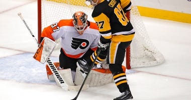 Pittsburgh Penguins' Sidney Crosby (87) tries to get a shot off in front of Philadelphia Flyers goaltender Brian Elliott (37) during the first period of an NHL hockey game in Pittsburgh, Tuesday, Oct. 29, 2019.